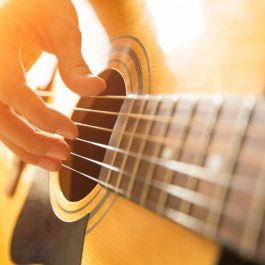 Female,Hand,Playing,On,Acoustic,Guitar.,Close-up.